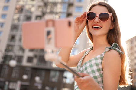 Beautiful young woman with sunglasses taking selfie outdoors 스톡 콘텐츠