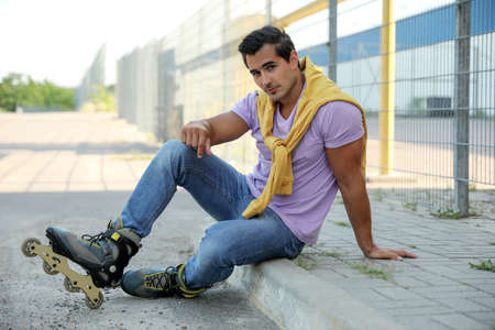 Handsome young man with inline roller skates sitting on curb outdoors Stock Photo