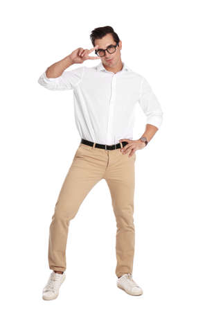 Handsome young man with glasses dancing on white background