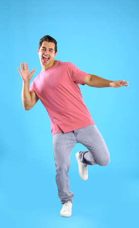 Handsome young man dancing on blue background Stock Photo