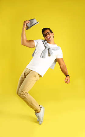 Handsome young man dancing on yellow background