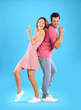 Beautiful young couple dancing on blue background