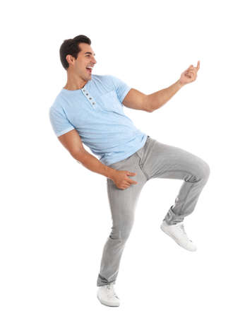 Handsome young man dancing on white background