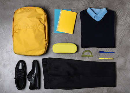 Flat lay composition with school uniform on grey background