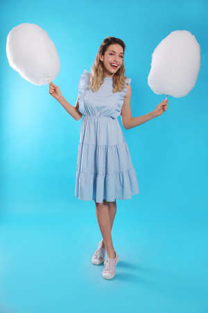 Full length portrait of pretty young woman with tasty cotton candy on blue background Imagens - 128609325