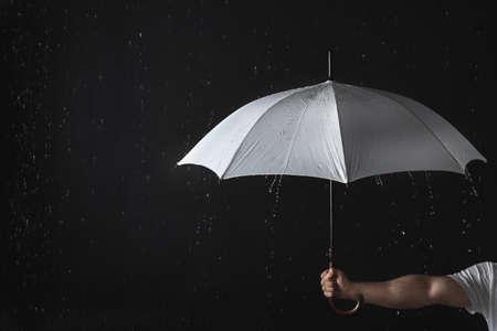 Man holding opened white umbrella under rain against black background, closeup
