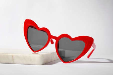 Stylish heart shaped sunglasses on board against white background Foto de archivo