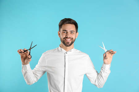 Young hairstylist holding professional scissors on color background Banco de Imagens