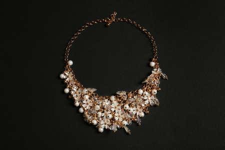 Stilvolle Halskette mit Edelsteinen auf schwarzem Hintergrund, Ansicht von oben. Luxusschmuck