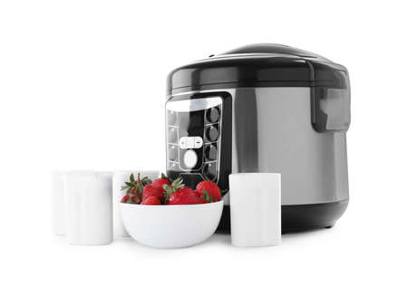 Modern multi cooker with cups of homemade yogurt and strawberries isolated on white Archivio Fotografico