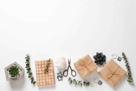 Composition of scissors and gifts on white background, top view