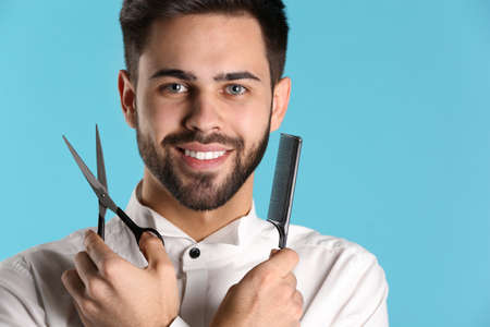 Young hairstylist holding professional scissors and comb on color background, closeup with space for text