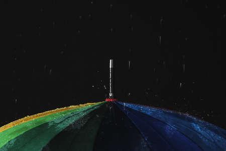 Opened color umbrella under rain against black background, closeup