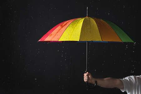 Man holding color umbrella under rain against black background, closeup