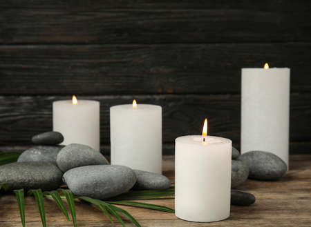 Burning candles, spa stones and palm leaf on wooden table