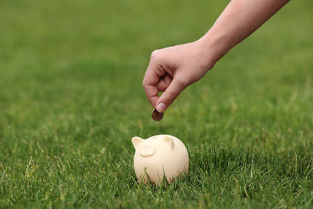 Young woman putting coin into piggy bank on green grass outdoors, closeup
