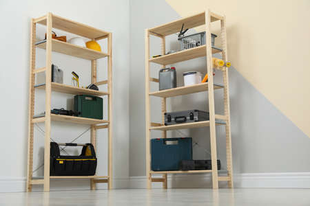 Wooden shelving units with different instruments near color wall. Stylish room interior