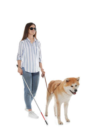 Blind woman with walking stick and dog on leash against white background