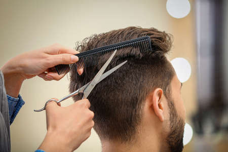 Barber making stylish haircut with professional scissors in beauty salon, closeup