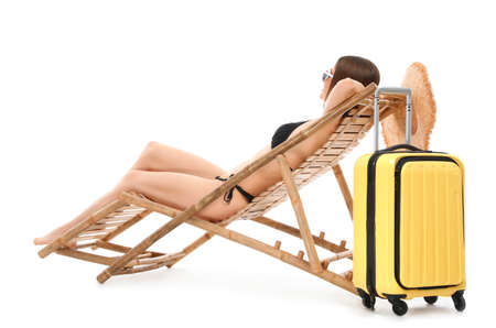 Young woman with suitcase on sun lounger against white background. Beach accessories