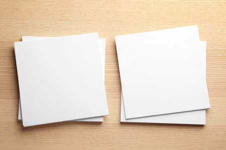 Blank paper sheets for brochure on wooden background, flat lay. Mock up 版權商用圖片