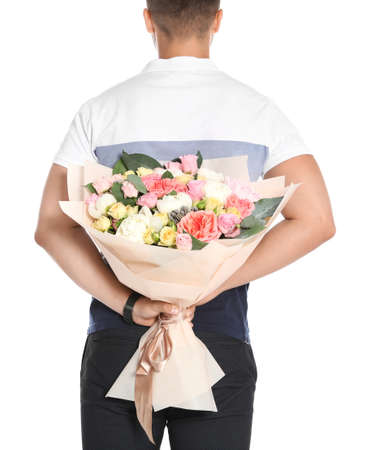 Young man holding beautiful flower bouquet on white background, back view