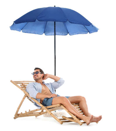 Young man on sun lounger under umbrella against white background. Beach accessories