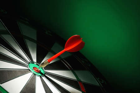 Red arrow hitting target on dart board against green background. Space for text