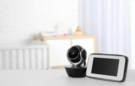 Baby monitor with camera on table in room, space for text. Video nanny Imagens