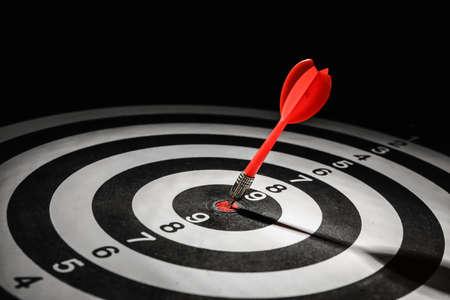 Flecha roja que golpea el objetivo en el tablero de dardos contra el fondo negro Foto de archivo