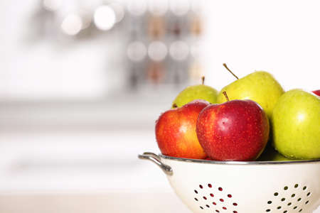 Colander with different sweet apples on table in kitchen, closeup. Space for text