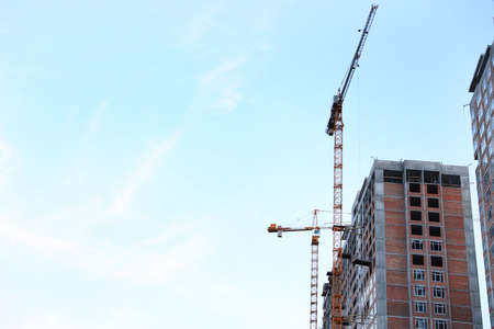 Construction crane and unfinished building against blue sky. Space for text