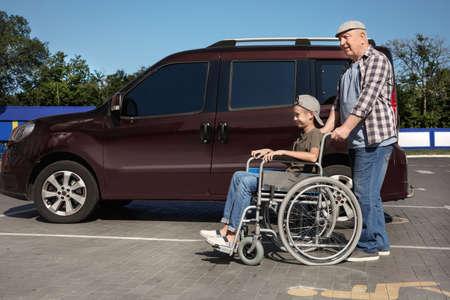 Senior man with boy in wheelchair near van on car parking