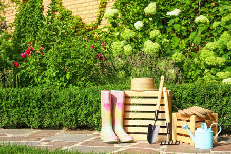 Wooden crates and gardening tools on stone path at backyard