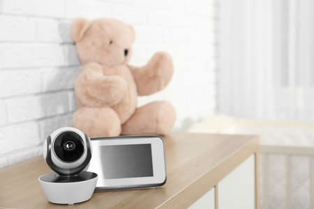 Baby monitor with camera and toy on chest of drawers in room, space for text. Video nanny Stock fotó