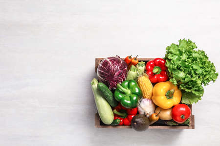 Crate with different fresh vegetables on light background, top view. Space for text Stockfoto