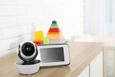 Baby monitor with camera and toys on chest of drawers in room, space for text. Video nanny