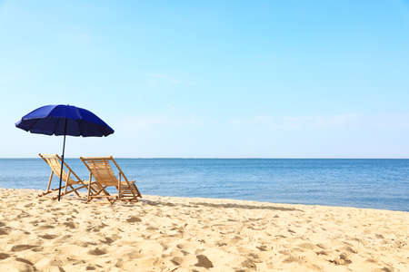 Empty wooden sunbeds and umbrella on sandy shore. Beach accessories Stock Photo