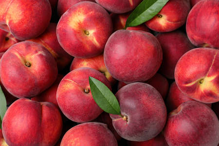 Delicious ripe peaches as background, top view