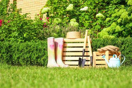 Wooden crates and gardening tools at backyard