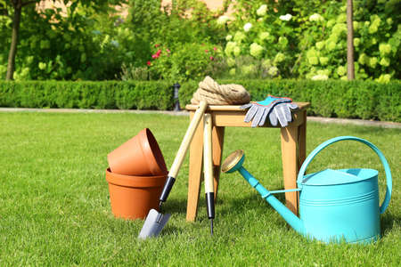 Set of gardening tools and stool on green grass Imagens