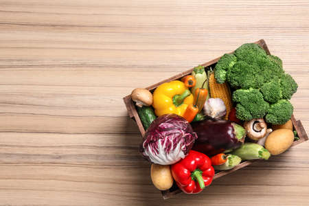 Crate with different fresh vegetables on wooden background, top view. Space for text