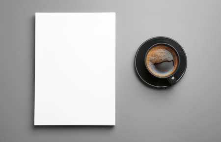 Blank paper sheets for brochure and cup of coffee on grey background, flat lay. Mock up