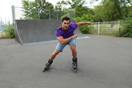 Handsome young man roller skating in park
