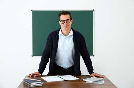 Junge Lehrerin steht in der Nähe des Tisches im Klassenzimmer