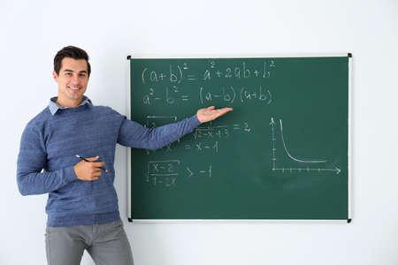 Young teacher explaining math formulas written on chalkboard in classroom