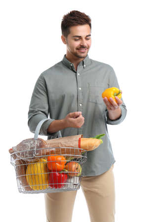Young man with bell pepper and shopping basket full of products isolated on white Banco de Imagens