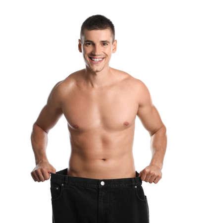 Jonge man met slank lichaam in oude grote maat jeans op witte achtergrond Stockfoto