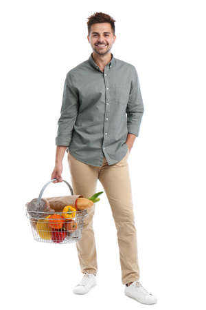 Young man with shopping basket full of products isolated on white Banco de Imagens