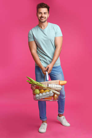 Young man with shopping basket full of products on pink background